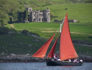 Galway Hooker sails by the Clifden Castle the home of the founder of Clifden John D'Arcy during the Clifden Traditional Boats Regatta in celebrations of 200 years of birthday of Clifden.